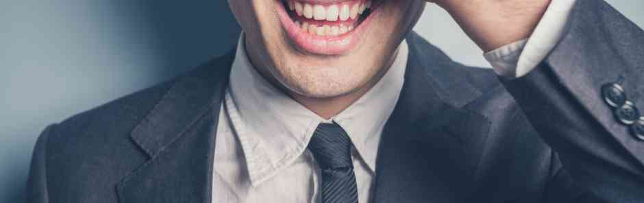 Aberdeen Advisors M&A: A happy young businessman is covering his face and eyes with his hand
